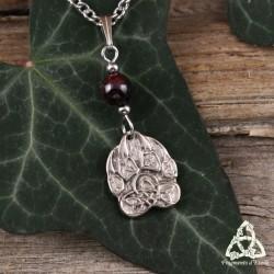 Collier médiéval et artisanal orné d'une Patte de Loup aux noeuds celtiques surmonté d'un Grenat rouge foncé.