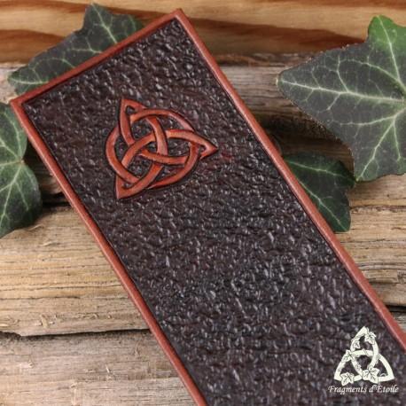 Marque page artisanal médiéval en cuir repoussé marron foncé et brun orné d'une Triquetra celtique pour votre grimoire.