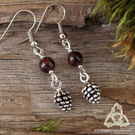 Boucles d'oreilles poétiques et nature ornées d'une pomme de pin argentée surmontée d'une perle de Grenat rouge foncé.