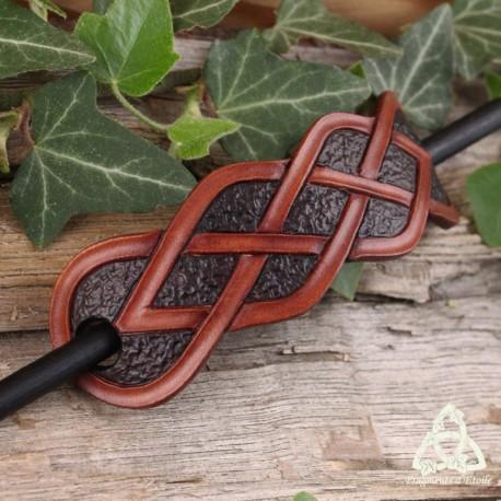 Barrette artisanale en cuir ornée d'entrelacs celtiques infinis marron sur un fond brun foncé texturé.