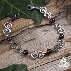 Bracelet médiéval et féerique Faerell orné de Spirales argentées entourées de perles de Grenat rouge foncé.