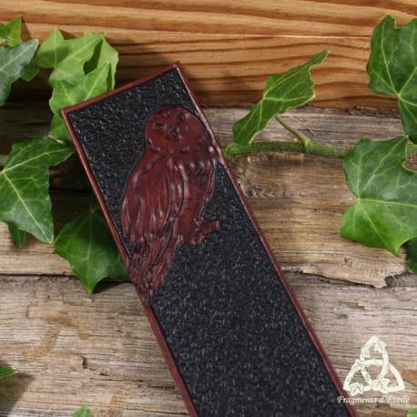 Marque page artisanal et médiéval en cuir repoussé orné d'un Hibou Harfang  au pelage duveteux foncé sur un rocher.